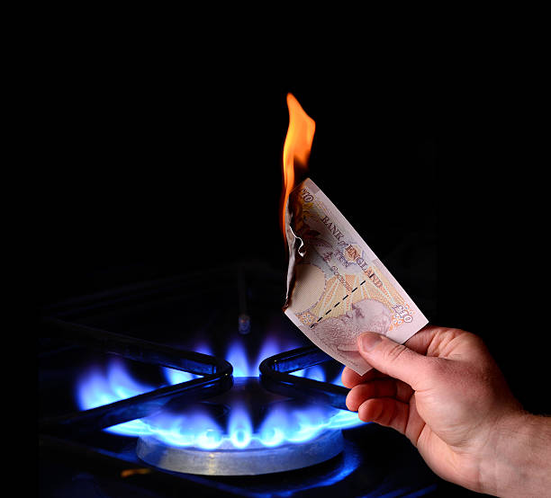 money to burn Money to burn! energy cost concept of burning a note on a gas fire money to burn stock pictures, royalty-free photos & images