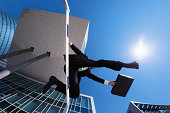 businessman with case jumping over hurdle at blue sky and office buildings