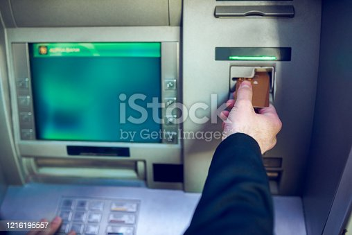 Closeup shot of an unrecognisable businessman making a transaction at an ATM