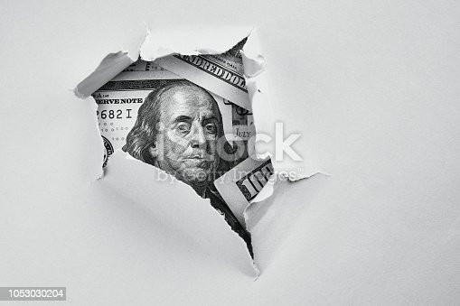 Bill of one hundred dollars under holed paper