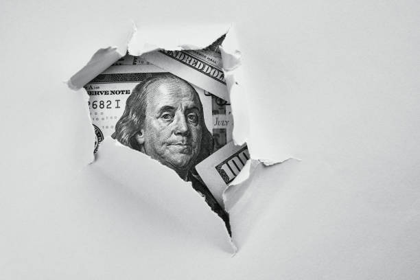Money under holed paper Bill of one hundred dollars under holed paper benjamin franklin stock pictures, royalty-free photos & images