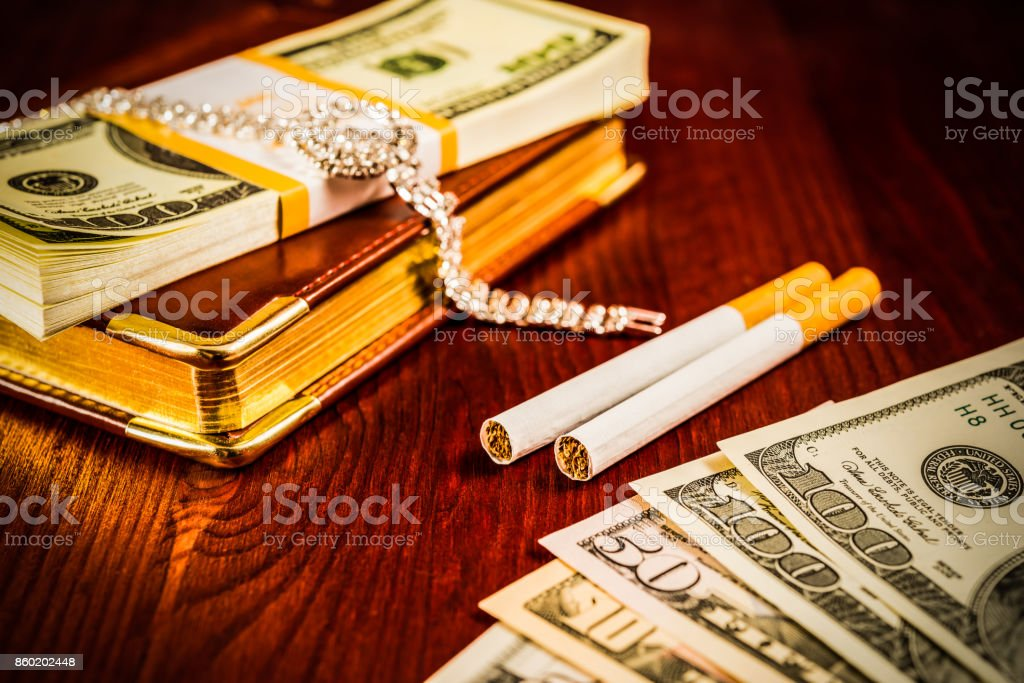 Money with a leather diary and cigarettes with jewellery stock photo