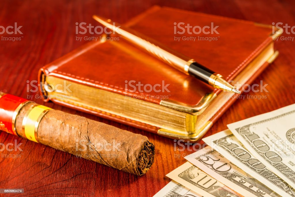 Money with a leather diary and cuban cigar with golden pen stock photo