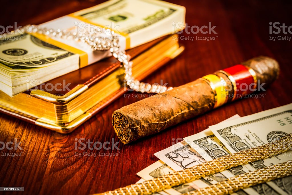 Money with a leather diary and cuban cigar with jewellery stock photo