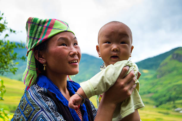 h'mong ethnic minority woman with her son in mucangchai, vietnam. - minority stock photos and pictures