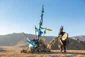 MONGOLIA - CIRCA NOVEMBER 2019 : mongolia shaman performed spiritual around Ovoo or Shaman's Shrine at the top of moutain and warm sunset
