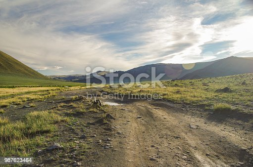 istock Mongolian Altai. Dirt road and mountain valley in beams of the evening sun. Smoking chimney of traditional yurt nomads. Nature and travel. Mongolia 987623464