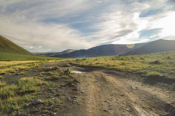 altai mongol. estrada de terra e vale montanhoso em raios de sol de noite. chaminé de nômades tradicional tenda a fumar. natureza e viagem. mongólia - estrada em terra batida - fotografias e filmes do acervo
