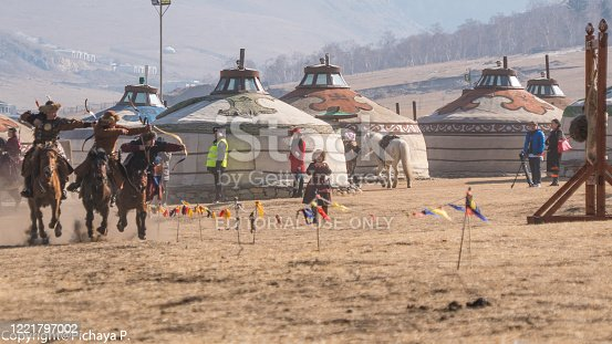ULAANBAATAR, MONGOLIA - MARCH 5 2019 : Mongolian Archery people in tradition clothes on horseback riding and shooting arrow from at village Ger in Mongolia.