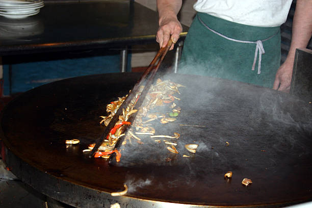 Mongolian BBQ A picture of a chef cooking a meal on a 'Mongolian BBQ' grill. Focus is on the food bwteen the tongs. independent mongolia stock pictures, royalty-free photos & images