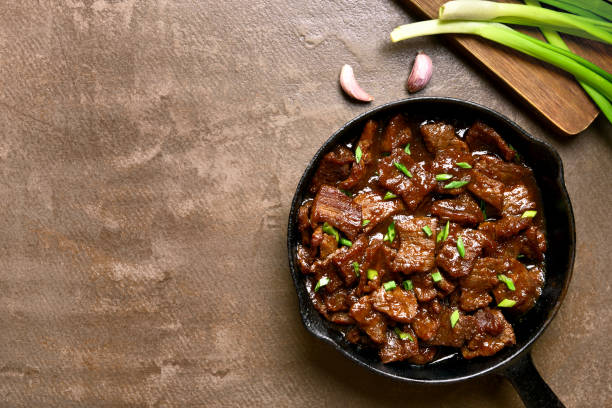Mongolian beef Beef stewed in soy sauce with spices in asian style on brown background with copy space. Mongolian beef. Top view, flat lay mongolian culture stock pictures, royalty-free photos & images