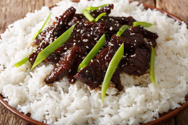 Mongolian beef with sauce and garnish of rice macro. horizontal Mongolian beef with sauce and garnish of rice macro on a plate. horizontal mongolian culture stock pictures, royalty-free photos & images