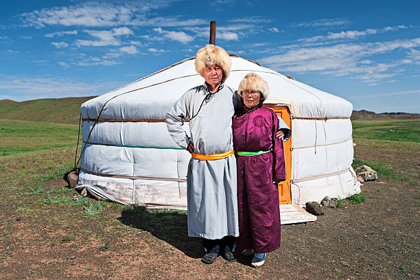 Mongolian couple in national clothing next to ger Mongolian couple in national clothing, ger (yurt) in the background.http://bhphoto.pl/IS/mongolia_380.jpg mongolian culture stock pictures, royalty-free photos & images
