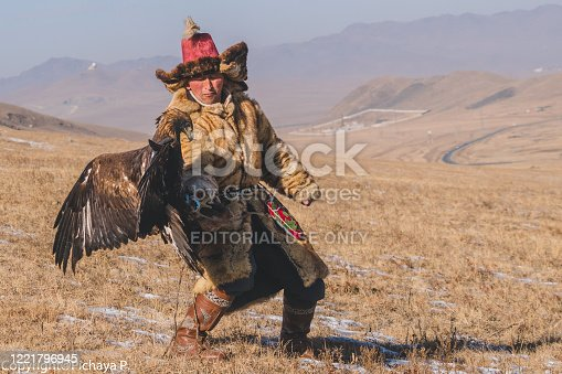 ULAANBAATAR, MONGOLIA - MARCH 5 2019 : Mongolian eagle hunter. Mongolia people in traditional clothes controls the eagle hunt by the hand.eagle's is preparing to fly and hunting animals.