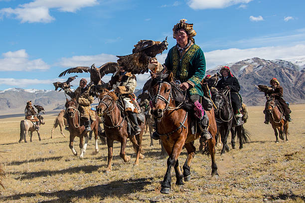Mongolian eagle hunters riding to the festival. Sagsay, Mongolia - September 22, 2012: Mongolian eagle hunters riding to the festival. A group of mongolian eagle hunter  from Kazakh tribe is riding to the eagle hunter festival of Sagsay with their  golden eagles on the arm. They wear their  traditional skin clothes, which are typical for western Mongolia, Altai area.Kazakh people in  the western part of mongolia domesticate female golden eagles for hunting. By this eagles they are hunting hare, foxes and even wolves during the very cold winter time. independent mongolia stock pictures, royalty-free photos & images