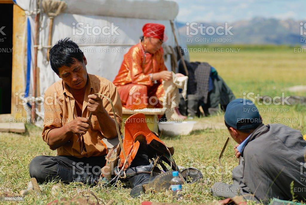Mongolian family members fix traditional horse saddle and do housework in Kharkhorin, Mongolia. stock photo