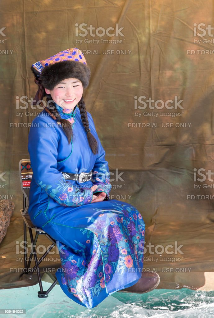 mongolian girl dressed in traditional clothing on a frozen lake stock photo