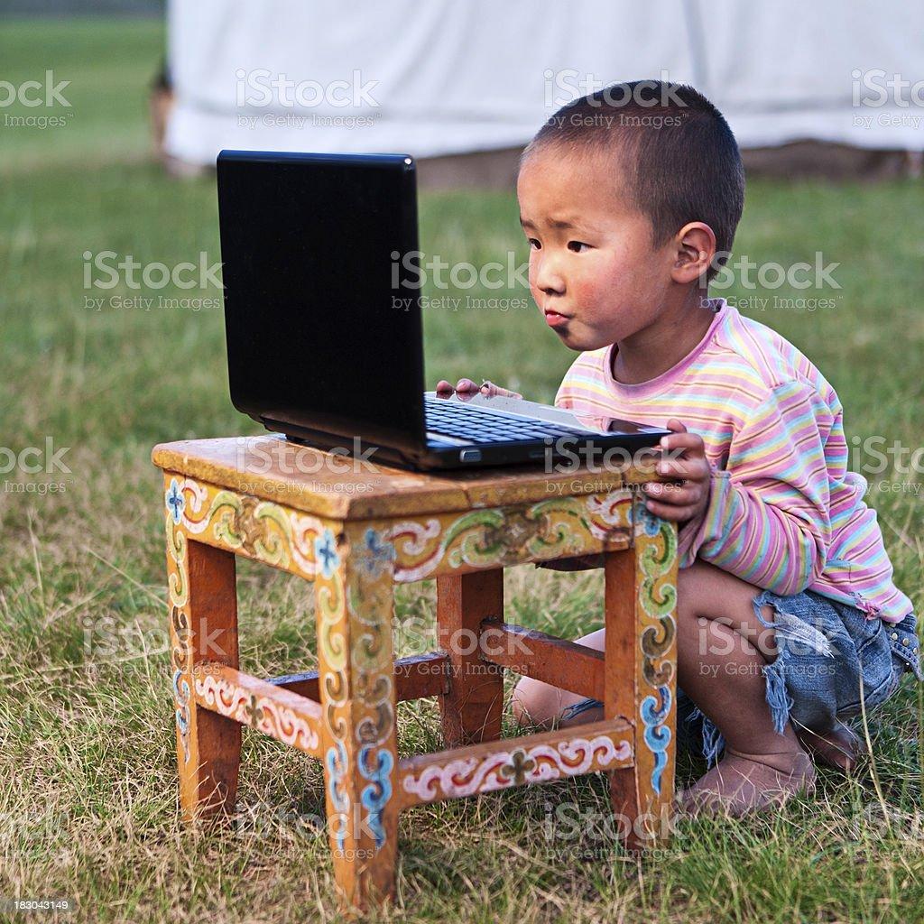 Mongolian litte boy using laptop royalty-free stock photo