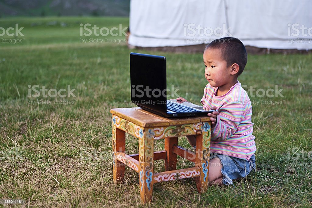 Mongolian little boy using laptop royalty-free stock photo