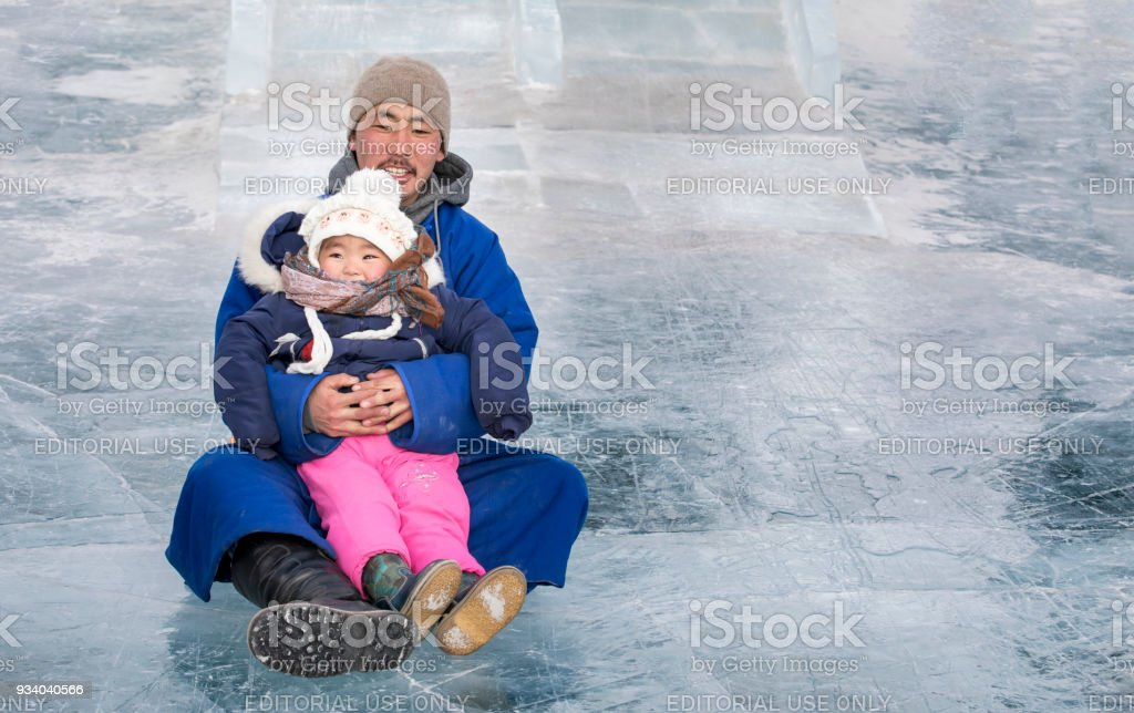mongolian man coming down a slide with his daughter stock photo