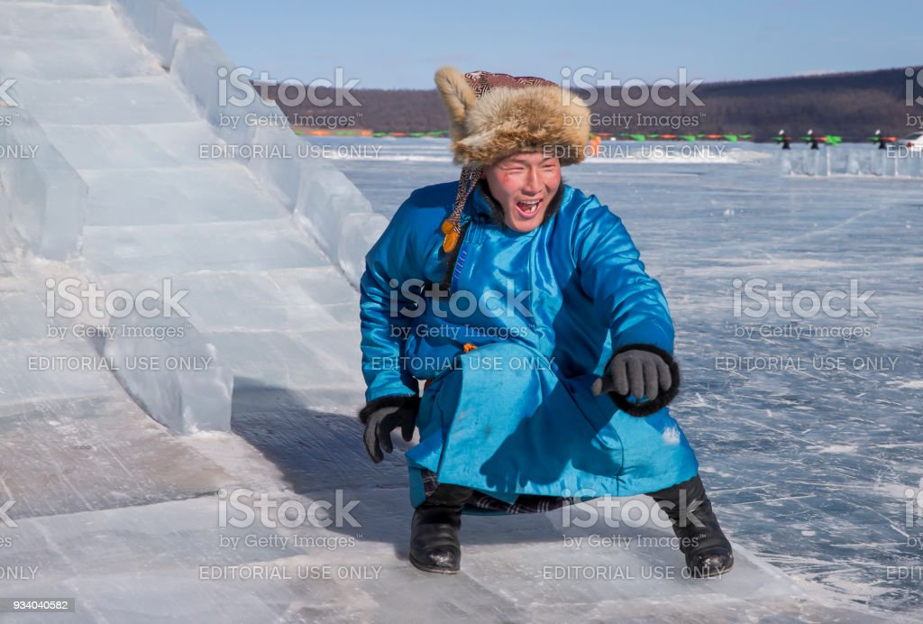 Mongolian man dressed in traditional clothing on a frozen lake, coming down a slide made of ice stock photo