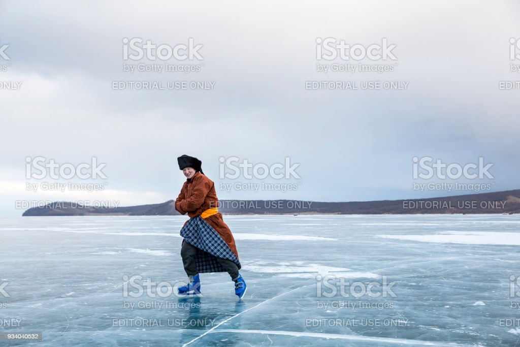 mongolian man dressed in traditional clothing skating on a frozen lake Khuvsgul in northern Mongolia stock photo