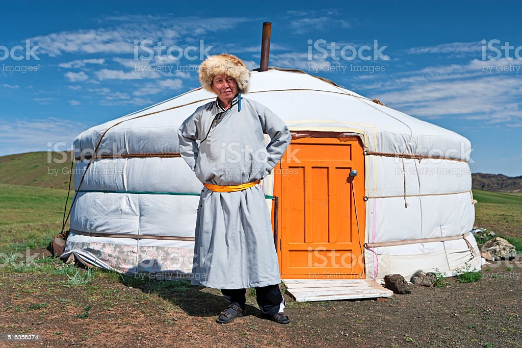 Mongolian man in national clothing standing next to ger stock photo