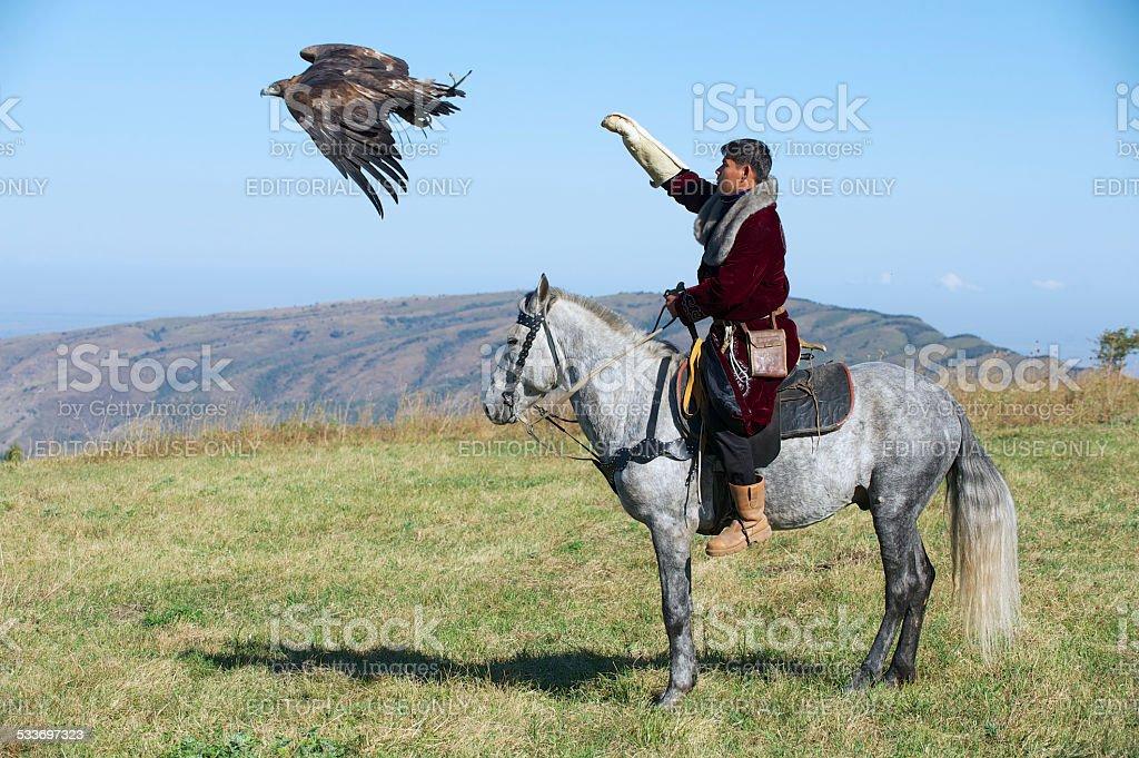 Mongolian man launches golden eagle circa Almaty, Kazakhstan. stock photo