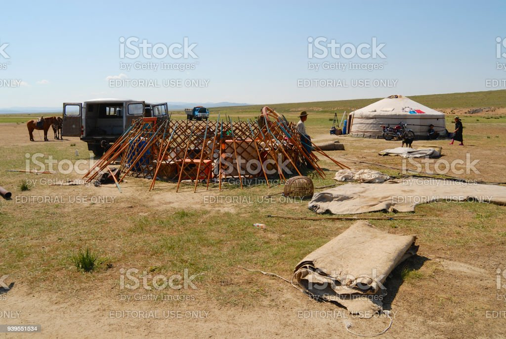 Mongolian men assemble yurt in steppe, circa Harhorin, Mongolia. stock photo