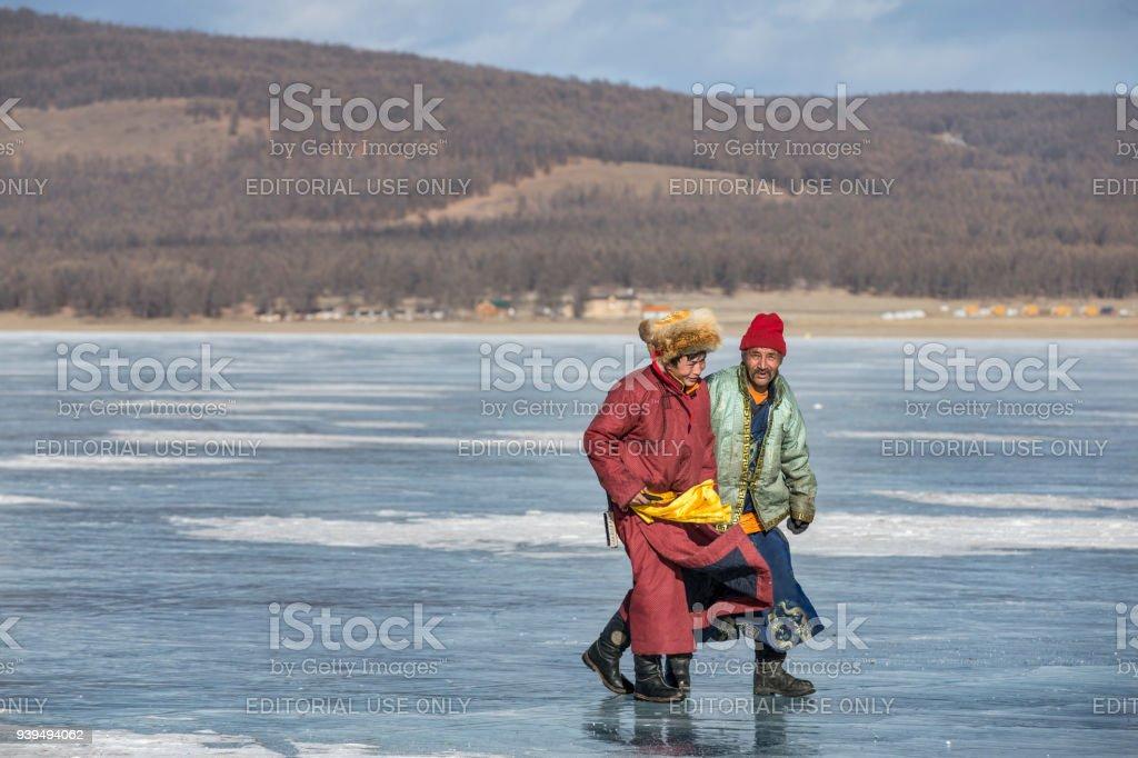 mongolian men in traditional clothing walking on frozen lake Khovsgol stock photo