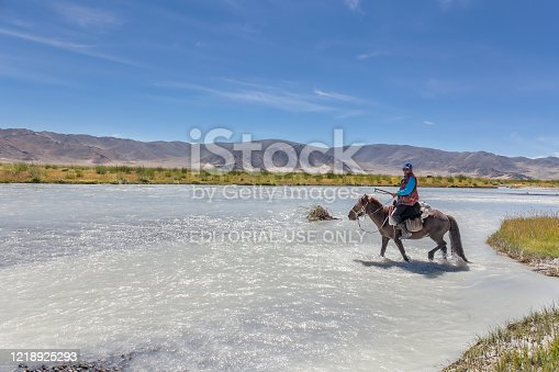 istock Altai, Mongolia - June 14, 2017: Mongolian nomad crosses a white mountain river on a horse. 1218925293