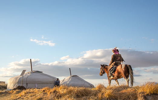 Bayan Ulgii, Mongolia, October 2nd, 2015: Old eagle hunter with his Altai Golden Eagle on his horse, going back home