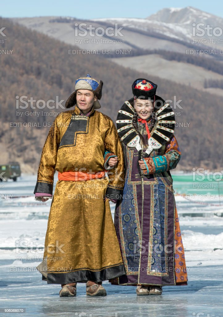 mongolian people dressed in traditional clothing on a frozen lake stock photo
