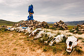 Mongolian stone shrine (ovoo) with ceremonial prayer flags or scarves (khadag) and horse skulls. These spiritual sites worship the mountains, sky and revered sky deity. Travelers walk clockwise three times adding a rock for a safe journey
