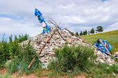 Mongolian stone shrine (ovoo) with ceremonial prayer flags (khadag). These spiritual sites worship the mountains, sky & sky deity. Travelers walk clockwise three times adding a rock for a safe journey.