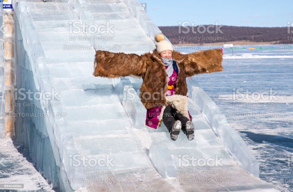 mongolian woman dressed in traditional clothing on a frozen lake, coming down a slide made of ice stock photo