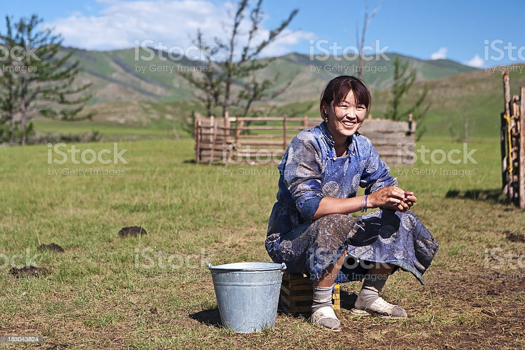 Mongolian woman in national clothing milking a yak stock photo