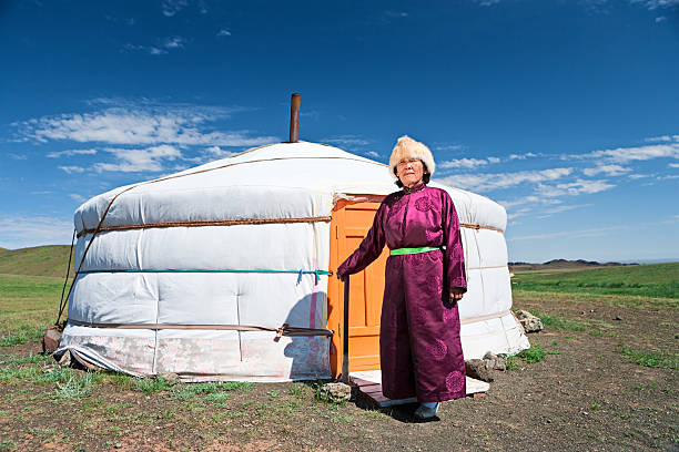 Mongolian woman in national clothing standing next to ger Mongolian woman in national clothing, ger (yurt) in the background.http://bem.2be.pl/IS/mongolia_380.jpg mongolian culture stock pictures, royalty-free photos & images