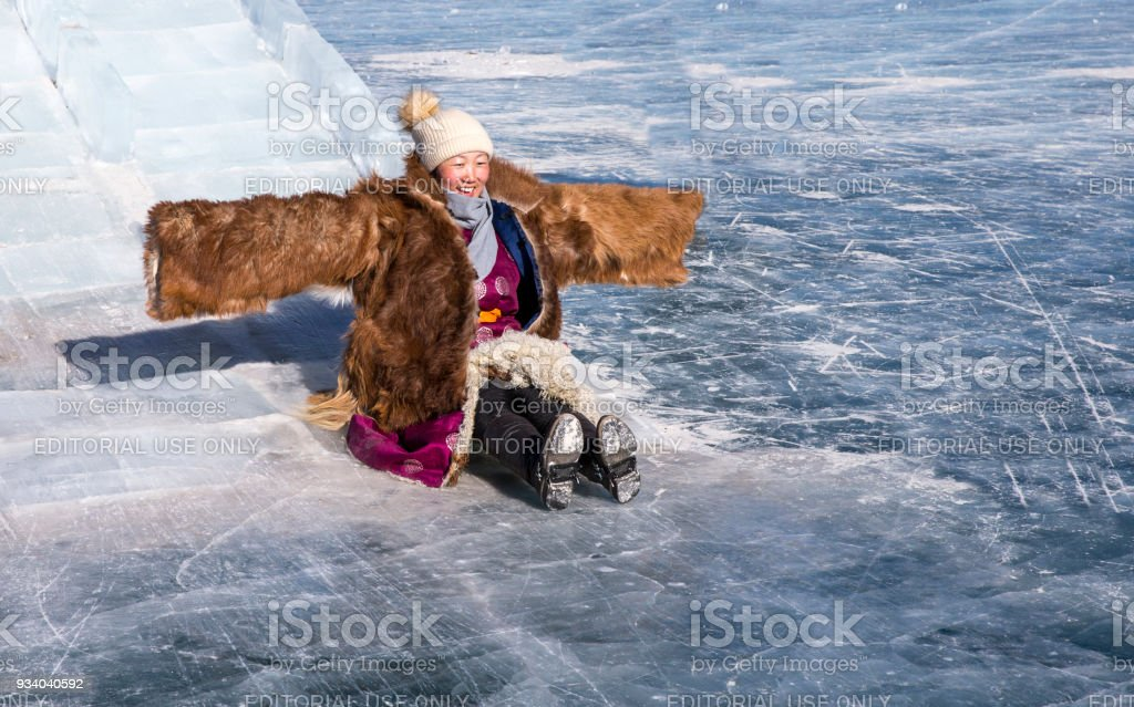 Mongolian woman on a frozen lake, coming down a slide stock photo