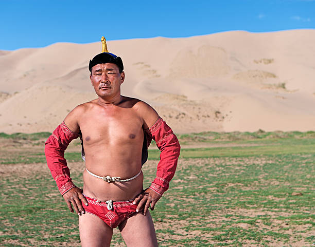 Mongolian wrestler posing during Naadam festival Mongolian wrestler posing during Naadam festival. He is standing on the grass, sand dunes on the background.http://bhphoto.pl/IS/mongolia_380.jpg mongolian culture stock pictures, royalty-free photos & images