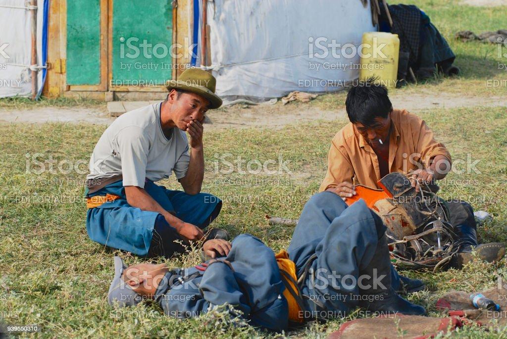 Mongolians fix traditional horse saddle, circa Harhorin, Mongolia. stock photo