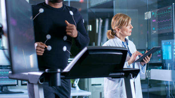 Monitor Shows EKG Reading of a Male Athlete Running on a Treadmill in the Background, Specialist Supervises Exercise Process, Controlling Physical Activity. Sport Science Theme. stock photo
