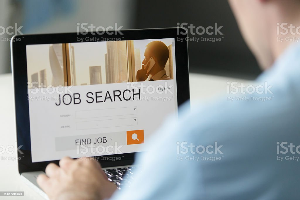 Monitor view over a male shoulder, job search title stock photo