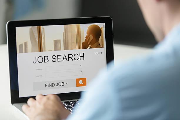 monitor view over a male shoulder, job search title - oficina de empleo fotografías e imágenes de stock