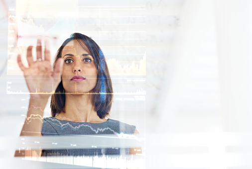 Shot of a young businesswoman using a digital interface while standing in a modern office