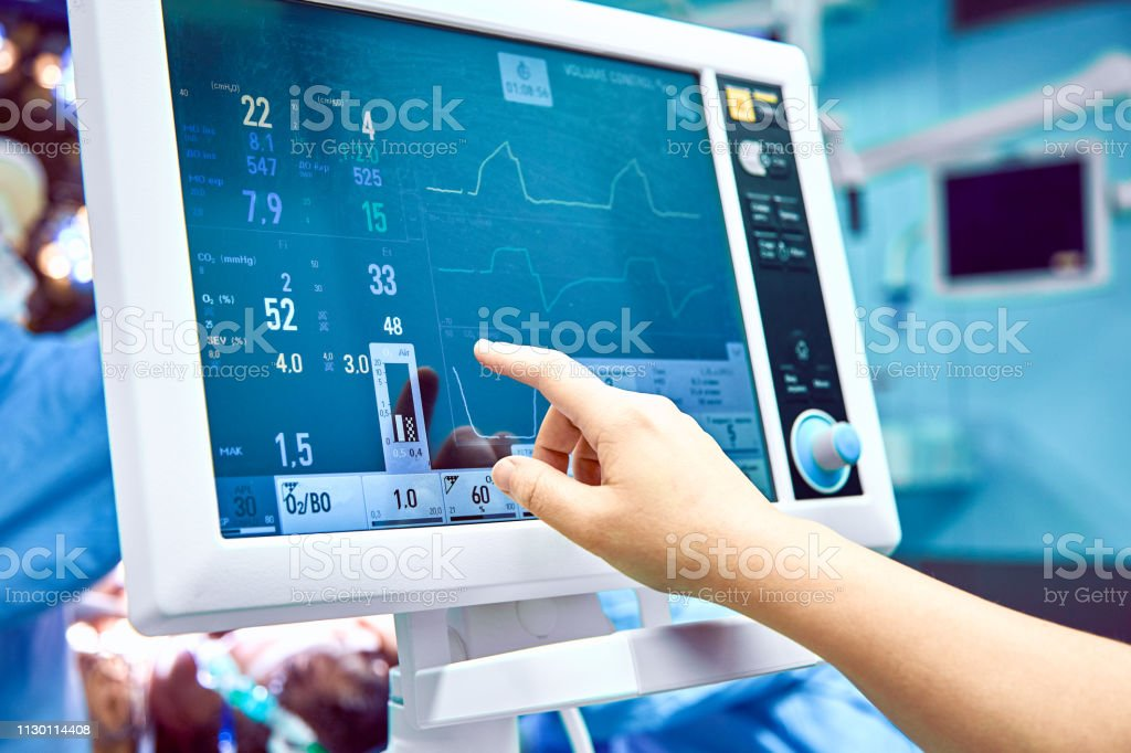 Monitoring patient's vital sign in operating room. doctor cheking at patient's vital signs. Cardiogram monitor during surgery in operation room. Monitoring patient's vital sign in operating room. Cardiogram monitor during surgery in operation room. Anesthesiologist Stock Photo