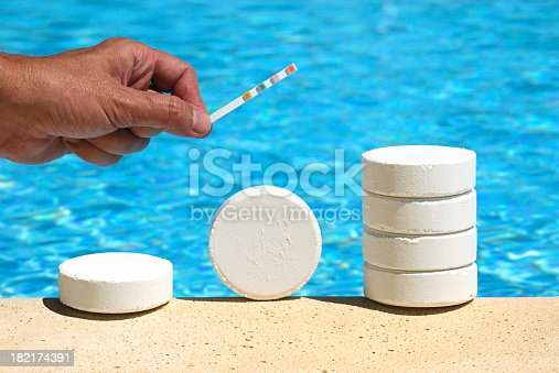 Pool Test Strip being held above Chlorine tablets - commonly used to sanitize swimming pool water