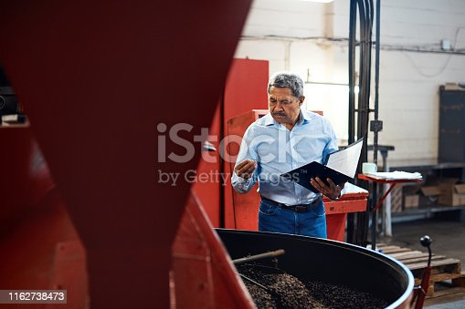 Shot of a mature man overseeing the production process in a coffee distribution warehouse