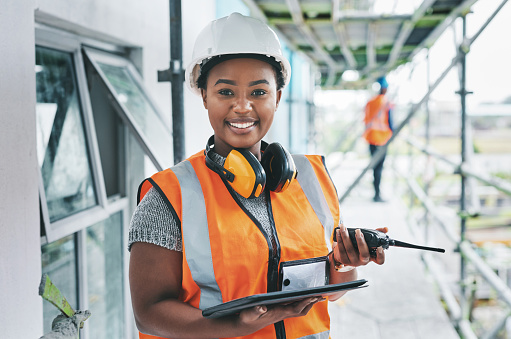 Portrait of a young woman using a digital tablet and walkie talkie while working at a construction site