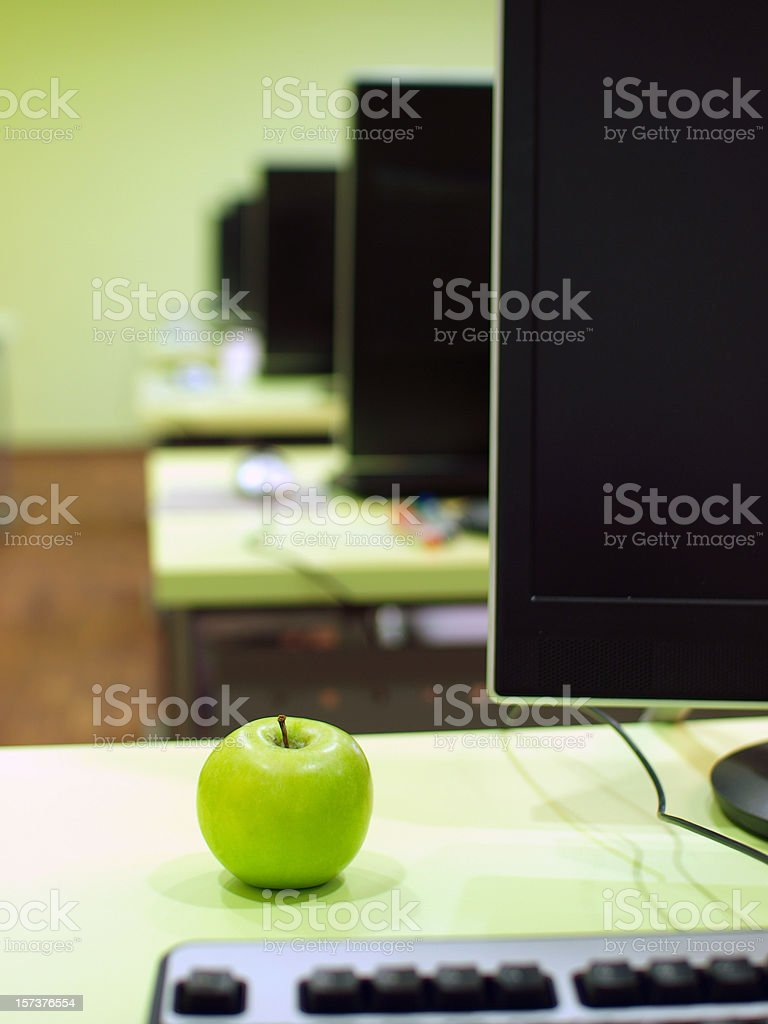 Monitors and Apple in Computer Lab - Royalty-free Business Stock Photo